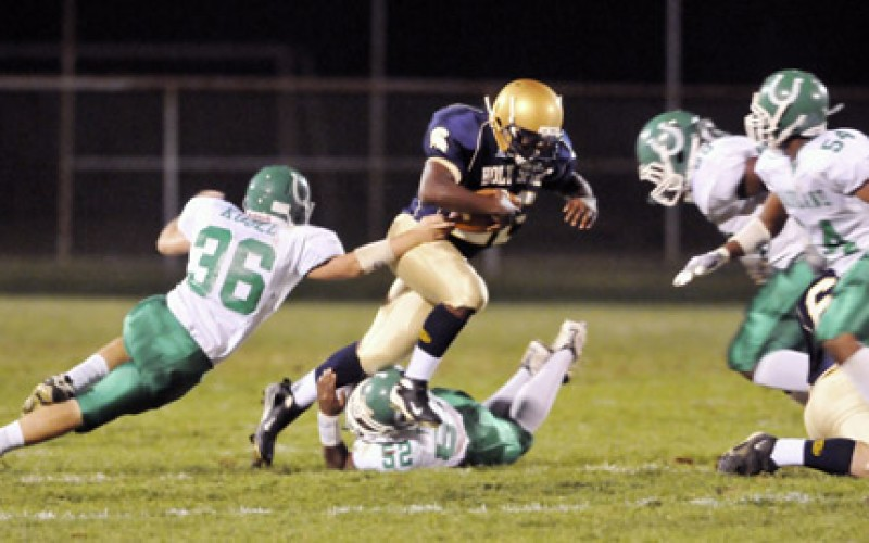 Holy Spirit's Donta Pollock gets through Mainland defenders on his way to a first down.