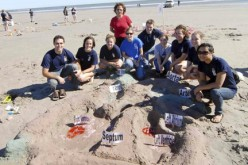 Med students teach kids in a sandy class