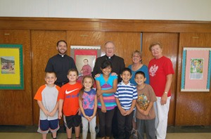 Photo by James A. McBride Bishop Dennis Sullivan and Father Kevin J. Mohan, parochial vicar at Our Lady of Peace Parish, Williamstown, pose for a photo with the 2nd grade religious education class at St. Joachim Parish, Bellmawr, on Sept. 23. It was the second religious education program the bishop visited during the week.