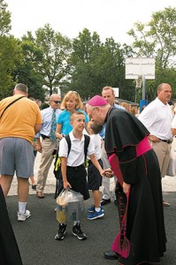 Photo by James A. McBride Bishop Dennis Sullivan greets fourth grader Patrick Alemi on the first day of school at St. Rose of Lima School in Haddon Heights on Sept. 3. Bishop Sullivan met with students, blessing them and the school community, at the start of a new school year. Behind Patrick are his parents, Sue and David, and his brother, second grader Sean.