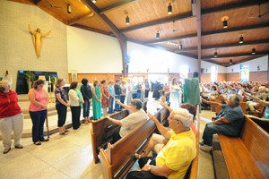 Photo by Alan M. Dumoff Father Grace Manano, associate pastor, and parishioners of St. Clare of Assisi, Gibbstown, bless catechists on Sept. 20.