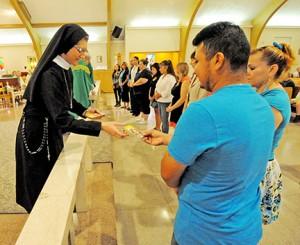 Photo by Alan M. Dumoff Sister Maria de Jesus hands out prayer cards at Holy Cross Parish, Bridgeton, on Sept. 21.