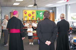 Photo by James A. McBride First grader James Barone of St. Rose of Lima, Haddon Heights, stands in front of Bishop Dennis Sullivan; Father Michael Romano, priest secretary; and Father Joseph Byerley, pastor, on Sept. 3, the first day of school. Bishop Sullivan greeted students and prayed with them for a good school year. At left is Karin Campanell, first grade teacher.