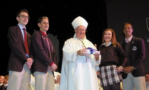 "Bishop Dennis Sullivan accepts a gift at Mass at Paul VI High School, Haddon Township, on Oct. 20, a day after the former pope's beatification and elevation to the title ""Blessed."" Pictured with the bishop are seniors, Rob Helsel, Anthony Leone, Marisa Tedesco and Mike Bizzoco. Photo by James A. McBride"