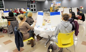 """Stephanie Zola, an art instructor at Camden Catholic High School, Cherry Hill, leads a class of adults gathered for """"a night of social painting"""" Nov. 7 at the school. With limited seating, and open only to individuals 21 or over, the evening, billed as Canvas Concoctions, included a cash bar with a selection of beers and cigars. Photo by Alan M. Dumoff"""