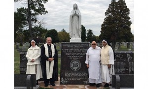Bishop Dennis Sullivan stands at the monument erected for nuns from the Monastery of the Perpetual Rosary who were re-interred in Calvary Cemetery, Cherry Hill, after the monastery closed last year. Pictured with the bishop are, from left, Sister Damien Marie; Dominican Father Anthony Cataudo, the monastery's last serving chaplain; and vicaress Sister Anna Marie Pierre.