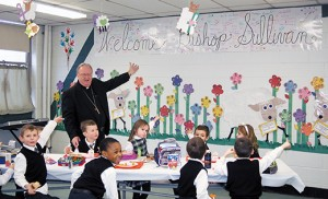 Bishop Dennis Sullivan and students gesture toward a sign they made welcoming him to Good Shepherd School, Collingswood, on Jan. 26. The bishop planned several school visits during Catholic Schools Week, celebrated nationally Jan. 25-31. Photo by James A. McBride