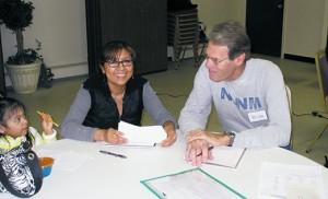 El voluntario Brian Brown ayuda a una estudiante durante la clase de ingles como segundo idioma.