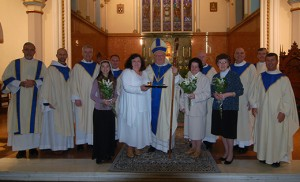 AnnaMae Muryasz stands to the left of Bishop Dennis Sullivan in the Cathedral of the Immaculate Conception, Camden, on Jan. 21 following the Rite of Consecration to a Life of Virginity. Also pictured, from left, are Deacon Jerry Jablonowski; Father Hugh McSherry, OFM; Father Michael Field; Christina Hip-Flores, Consecrated Virgin, Archdiocese of Santiago de Cuba; Father James Bartoloma; Dr. Jewel Brennan, Consecrated Virgin, Diocese of Trenton; Father Robert Hughes; Carolyn Blaszczyk, Consecrated Virgin, Diocese of Harrisburg; Father Nicholas Dudo; Deacon Michael Carter; and Father Joseph Wallace. Photo by James A. McBride