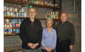 Joe and Bunny Franco of Ventnor have been running the food bank ministry at St. Nicholas of Tolentine Parish, Atlantic City, for 15 years. They are pictured with Msgr. William Hodge, pastor of St. Nicholas. Held on the third Monday of each month, food is distributed to an average of 225-250 people. The week before Thanksgiving, that number jumped to 300 and the numbers are expected to grow even larger as the checks from the newly unemployed casino workers begin to run out. Photo by James A. McBride