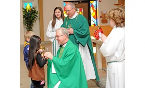Father Vincent G. Guest, pastor of Holy Cross Parish, Bridgeton, accepts the offertory gifts Feb. 1 at a Mass celebrating 50 years of Scouting in the community. Photo by Alan M. Dumoff, more photos http://ccdphotolibrary.smugmug.com