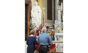 Laura and Nick Petrone of Egg Harbor Township pray before the start of the 30th annual memorial Mass honoring public safety personnel who have died in the line of duty. Msgr. William A. Hodge, pastor, celebrated the Mass March 15 at St. Nicholas of Tolentine Church, Atlantic City. Photo by Alan M. Dumoff, more photos ccdphotolibrary.smugmug.com