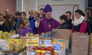 "Bishop Dennis Sullivan blesses donated food brought to the Catholic Community of the Holy Spirit, Mullica Hill, on March 1 for the FaithFULL Food Drive. The donations were later loaded onto trucks and taken to a food bank for distribution. The diocesan-wide event made ""a sizable impact"" on bringing relief for the hungry in South Jersey, said Michael Jordan Laskey, director of Life and Justice for the Diocese of Camden. Photo by James A. McBride"