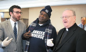 Photo by James A. McBride Impressed with Bishop Dennis Sullivan's New York origins, fellow Yankee fan Wayne Bowman has his picture taken with the bishop at the New Visions Homeless Day Shelter in Camden. Bishop Sullivan and Camden Diocesan representatives visited the shelter on March 23, a day dedicated to the memory of the Salvadoran Archbishop Oscar Romero.
