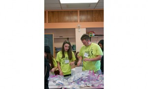 Photo by James A. McBride Carley Robinson, a member of the John Paul II high school youth group at Our Lady of Peace, Williamstown, makes care packages with Chris Myers, a parish volunteer, at the Diocesan Youth Congress March 22 at St. Charles Borromeo, Sicklerville.