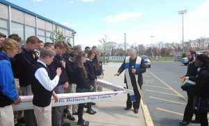 Bishop Dennis Sullivan blesses two new crew boats during a visit to Holy Spirit High School, Absecon, on April 24. One of the boats is named for the bishop, and the other is named for Pope Francis. Photo by James A. McBride