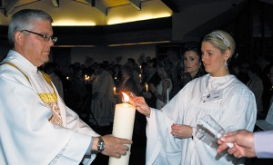 Crystal Jeffries receives light from the Paschal Candle held by Deacon William Slaven during the Easter Vigil April 4 at St. Andrew the Apostle Parish in Gibbsboro. Celebrated by Bishop Dennis Sullivan, the vigil at St. Andrew's joined other Christian communities around the world in recalling Jesus' Resurrection. Jeffries, a catechumen in the parish's Rite of Christian Initiation of Adults (RCIA), received the sacraments of initiation during the vigil and entered into full communion with the Catholic Church. Photo by James A. McBride