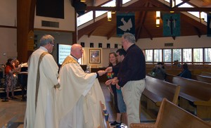 Father Robert Hughes, vicar general of the Diocese of Camden, accepts the offertory gifts from Cheryl LaSpada and her son Tyler and Stephen Francis Kline during a diocesan Eucharistic celebration in observance of Autism Awareness Month April 12 at Holy Family Parish, Sewell. At left is Deacon Gerald J. Jablonowski, director of Home and Parish-based Healthcare Services for the diocese. Photo by James A. McBride