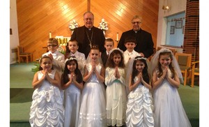 Bishop Dennis Sullivan and Msgr. Joseph V. DiMauro, pastor of Holy Angels Parish, Woodbury, stand with children following the May crowning at Holy Trinity Regional School, Westville Grove, on May 21. The month of May is devoted to Mary and is traditionally celebrated with a crowning and praying of the rosary. Photo by Father Michael M. Romano