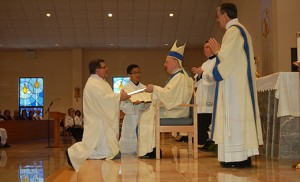 Bishop Sullivan presents the Book of the Gospels to newly-ordained Deacon Robert Iuliucci.