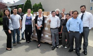 Standing with 3,540 copybooks that will be donated to local children are staff members of Catholic Charities' Refugee and Immigration Services program and representatives of CRW Graphics, the donors.