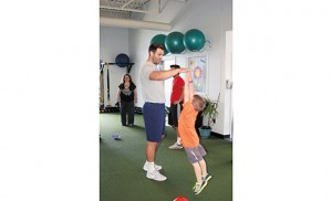 On May 17, Baltimore Ravens quarterback, and Audubon native, Joe Flacco visited Evolution Fitness in Cherry Hill, helping children get fit, and raising money for St. John of God Community Services in Westville Grove. Photos: Flacco encourages a youth to reach for the sky, or his hand and the Super Bowl-winning quarterback leads the group in a balancing activity. Photos by James A. McBride