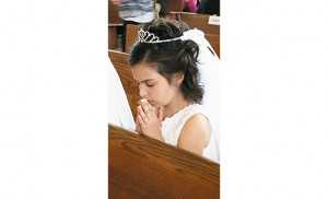 Gabriella Elizabeth Gross prays after receiving her first Communion May 9 at Annunciation Church, St. Joachim Parish, Bellmawr.