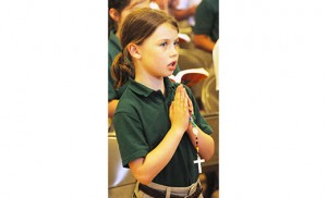 Imogene Nuss, a third grade student at Bishop McHugh Regional School, Cape May Court House, prays the rosary May 19 during a prayer service when the International Pilgrim Virgin Statue of Our Lady of Fatima was brought to the school. Photo by Alan M. Dumoff