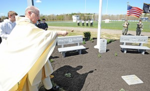 Augustinian Father Donald Reilly, resident of St. Augustine Prep, blesses the Richland school's new Veterans Memorial, which was unveiled during a ceremony on April 29. The memorial honors two school alumni: 1st Lieutenant Salvatore S. Corma II, Class of 2004 and graduate of the 2008 United States Military Academy class, who died at the age of 24 in 2010, while jumping on an improvised explosive device in Afghanistan to save his men; and PFC Edward K. Miller, a 1966 graduate of St. Augustine, who died in 1968, while serving in the Vietnam War. Photo by Alan M. Dumoff, ccdphotolibrary.smugmug.com