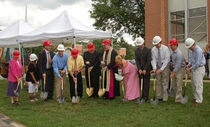 Bishop Dennis Sullivan, with Father Thomas Newton, pastor, to his left, and surrounded by parish and school staff and community members, breaks ground for the planned parish center and gymnasium at Christ Our Light Parish in Cherry Hill, June 5. At far left is Sister Lydia Etter, OSF, principal of Resurrection Catholic School. Photo by James A. McBride