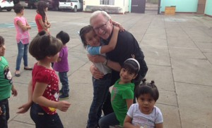 Father Vincent G. Guest is pictured with children of an orphanage in Mexico.