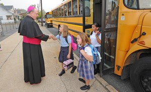 The 2015-16 school year began before Labor Day this year at Catholic schools in the Camden Diocese with students arriving for classes on Wednesday, Sept. 2. Bishop Dennis Sullivan welcomes students as they get off the bus at Bishop Schad Regional School, Vineland. Photo by Alan M. Dumoff, ccdphotolibrary.smugmug.com