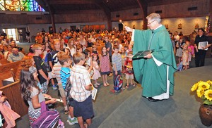 Father Perry Cherubini, pastor, blesses the backpacks of students at the family Mass at St. Elizabeth Ann Seton Church, Absecon, on Sept. 6. Photo by Alan M. Dumoff, more photos ccdphotolibrary.smugmug.com