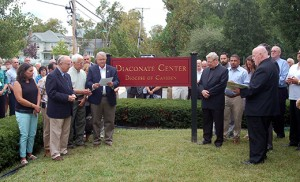 Father Robert Hughes, Vicar General for the Diocese of Camden, blesses the new Diaconate Center in Vineland on Sept. 12, its first day of formation sessions for men studying for the permanent diaconate. The dedication followed an open house of the new facility, the site of the former Sacred Heart High School. It includes classrooms, a library and a chapel. The Parish of Christ, the Good Shepherd, collaborated with the diocese on opening the new center. Next to Father Hughes is Msgr. John Burton, pastor of Christ, the Good Shepherd. Standing at left is Deacon Leo McBlain, director of personnel for the permanent diaconate. Not pictured is Deacon Michael J. Carter, director of formation for the permanent diaconate. Photo by James A. McBride