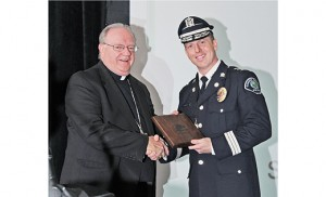 Bishop Dennis Sullivan congratulates Camden County Police Chief Scott Thomson, who accepted the Organizational Justice in Action Award for the Camden County Police Department at the annual Catholic Charities Justice for All dinner Sept. 17 at Adelphia Caterers, Deptford; Sister Graciela Rosas, left, recipient of the 2015 Individual Justice in Action Award, receives applause as she stands to accept her award. Photos by Alan M. Dumoff