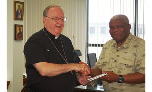 """Bishop Dennis Sullivan, who wrote the foreword to """"My First Missal,"""" congratulates Amam Acholonu, who wrote the book with his wife, Margaret. Photo by James A. McBride"""