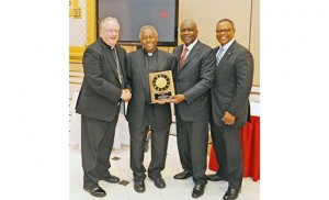 Msgr. Leonard G. Scott, retired pastor and former judicial vicar, accepts the Racial Justice Lifetime Achievement Award at the Racial Justice Commission Awards Dinner Sept. 10 at Adelphia Restaurant, Deptford. Pictured from left are Bishop Dennis Sullivan; Msgr. Scott; James E. Andrews, coordinator; and Curtis H. Johnson, Jr., chairperson. Msgr. Michael Doyle, pastor of Sacred Heart Parish, Camden, was the recipient of the Racial Justice Award, and Sister Karen Dietrich of Catholic Partnership Schools received the Many Faces in God's House Award. Photo by Alan M. Dumoff