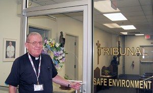 """A portrait of Pope Francis is visible in the background as Father David J. Klein, Judicial Vicar, Diocese of Camden, stands at the Tribunal door at the Pastoral Center, Camden. The pope approved rewriting sections of the Latin-rite Code of Canon Law and the Code of Canons of the Eastern Churches to make the annulment process quicker, less expensive and more pastoral. """"In the coming months new procedures and policies will be developed,"""" Bishop Dennis Sullivan said in a statement Sept. 8. """"I have asked the Diocesan Tribunal to prepare presentations for priests, deacons and the faithful before the beginning of December.""""  Photo by James A. McBride"""