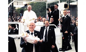 """Anne Hartman, principal of Christ the King School, Haddonfield, took this photo of Pope Francis enjoying the sight of a baby wearing a miter, the tall, pointed ceremonial cap worn as part of liturgical dress by a pope or bishop. She explains: """"I was blessed to be in the crowd down by Independence Hall today and stood right behind the barrier next to a couple who had a 4-month-old daughter who was dressed in white and was wearing a miter on her head. We joked and laughed all day that if we were lucky enough to actually be on the right street for the pope to pass by we would try to get his attention for him to see the baby and wave. Well, Pope Francis saw her, and he laughed out loud, stopped the car, sent his guard to get her and then sent the baby back with a message thanking the mother for making him laugh and that he appreciated a sense of humor."""""""