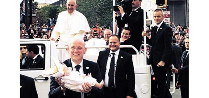 The baby wearing a miter gets the pope's attention