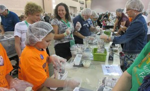 Christy Wimberg (third from left) of St. Gianna Beretta Molla Parish, Northfield, helps pack meals that will be delivered to West African nation Burkina Faso. The Catholic Relief Services project took place during the World Meeting of Families at the Pennsylvania Convention Center in Philadelphia last week. Photos by Joanna Gardner Tyler Wimberg, below, and his brother Connor work the line with their mother.