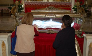 "Above, Women pray before the relics of Saint Maria Goretti at Saint Peter Church, Merchantville, on Oct. 7. Right, the major relics, which are virtually all of the skeletal remains of the saint, known as the ""patroness of purity,"" made a one-day stop at the church while on a U.S. ""pilgrimage of mercy"" this fall. Photos by James A. McBride"
