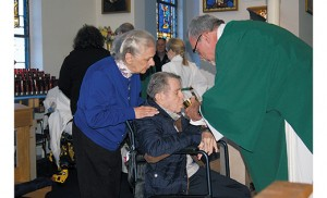 Joseph Kronberger of Franklinville receives Communion from Deacon Jerry Jablonowski, director of VITALity Catholic Health Care, Diocese of Camden, during a Mass for the sick Nov. 20 at Our Lady of Peace Parish, St. Mary Church, Williamstown. Also pictured is Dominica Kronberger. Bishop Dennis Sullivan celebrated the Mass, which was sponsored by the diocese's Home and Parish Healthcare Services, especially for individuals dealing with Alzheimer's and their family and caregivers. Photo by James A. McBride