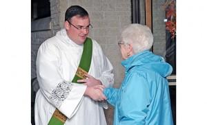 Rev. Mr. Edward Kennedy greets a parishioner after Mass at St. Raymond Church, St. John Neumann Parish, North Cape May, on Nov. 7. Photo by Alan M. Dumoff