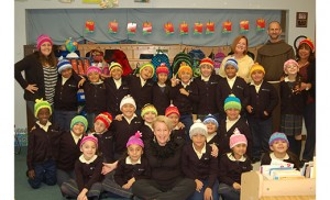"Roslyn Rothenberg (seated, first row) of Haddon Heights knit 23 hats for the first grade class of St. Anthony of Padua School, Camden, as well as the principal and teachers. ""It was a lot of fun to do the knitting,"" she said. ""Giving them to the children and seeing their joy is on my life list of best things ever."" Photo by James A. McBride"