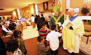 El Obispo Dennis Sullivan y el Padre Robert Hughes, vicario general, saludan a los niños durante la celebración hispana anual de la Diócesis de Camden, celebrada el 8 de noviembre en la Parroquia Divina Misericordia en Vineland. Photos by Alan M. Dumoff