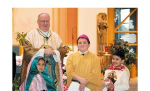 Bishop Dennis Sullivan lets sixth grader Tyler Strickland, who portrayed a Mexican bishop in a skit about Our Lady of Guadalupe, wear his zucchetto, the skullcap worn by Catholic clergy. First grader Jackelin Rangel took the part of Our Lady of Guadalupe, and Christian Rangel, also a first grader, was Juan Diego at Saint Luke Church in Stratford, part of Our Lady of Guadalupe Parish, Lindenwold. The children are students of John Paul II Regional School, Stratford. Photo by James A. McBride