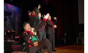Comedian Jim Labriola, kneeling, joins the New York Tenors onstage at Investors Bank Performing Arts Center in Sewell Dec. 5. The Magic of Christmas concert benefited Catholic school students, with the money raised going to the South Jersey Scholarship Fund. Photo by James A. McBride