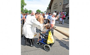 Father Joseph Capella blesses a woman at the Our Lady of Mount Carmel Festival in Hammonton in 2014. The priest is the pastor of Our Lady of Guadalupe Parish in Lindenwold, a diverse parish with a large number of Latino and Burmese members. Photo by Alan M. Dumoff