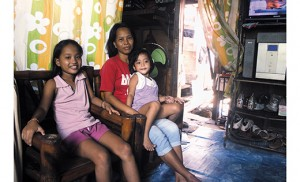Julie Martinez and two of her children, Sharmine, age 11, and Aubrey, age 3, in their home in Metro Manila, Philippines. The house's wooden foundation has become dangerously weak because of water damage. Photo by Joanna Gardner